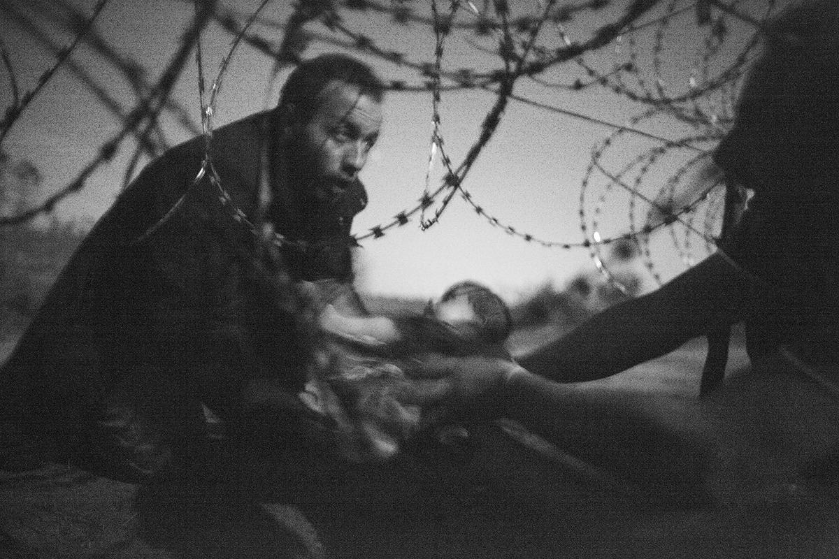 A WorldPress fotó 2015 első helyezett fényképe. A Budapesten élő ausztrál fényképész, Warren Richardson 2015 augusztus 28-án készítette a fényképet a hajnali órákban a Hold fényénél, mint egy menekült nyújtja át gyermekét a szögesdrót kerítésen. Fotó: Warren Richardson