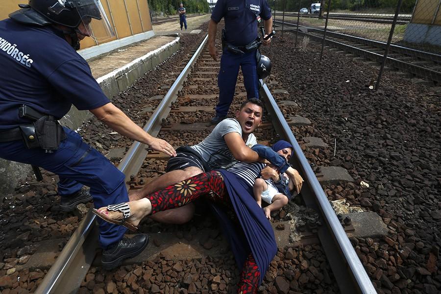 Egy szíriai férfi a sínekre vetette magát tiltakozásképpen az ellen, hogy családjával együtt tranzittáborba szállítsák őket. Fotó: Balogh László