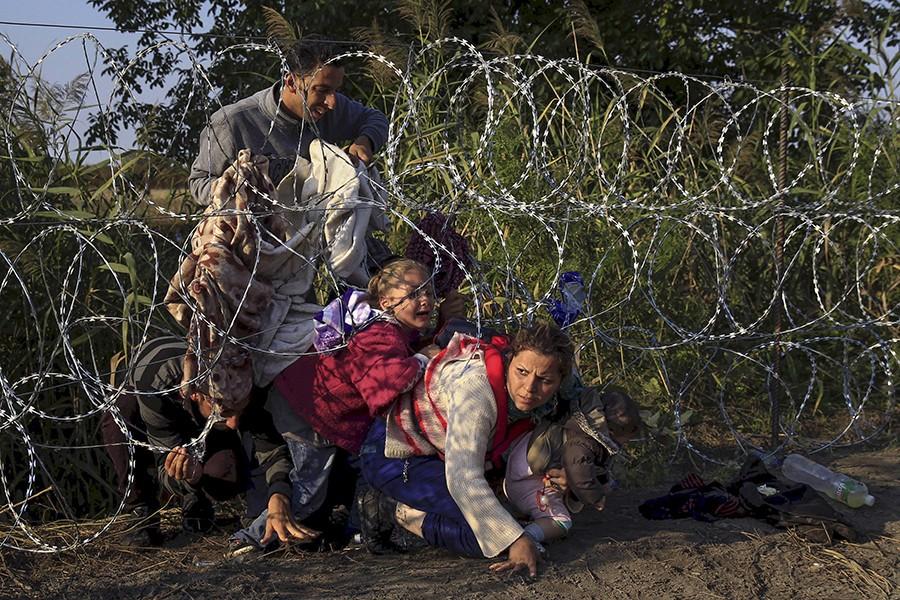 Röszke közelében a szögesdrót akadályon áthatol egy szíriai család. Fotó: Szabó Bernadett